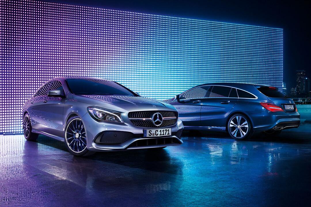 två-stycken-mercedes-CLA-Cupé-står-parkerade-i-blått-ljus
