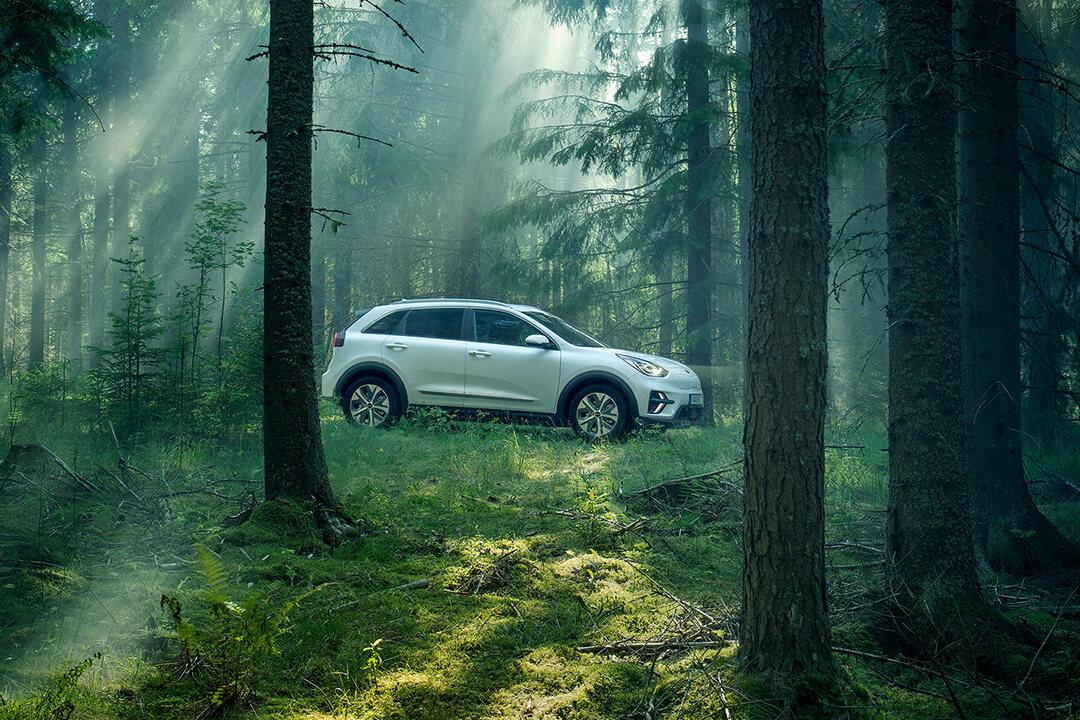 kia_niro_ev_-står-i-en-glänta-i-skogen