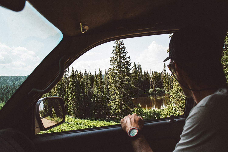 en-man-kollar-på-naturen-från-sin-bil