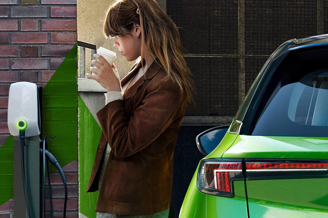 kvinna-dricker-kaffe-och-laddar-bilen